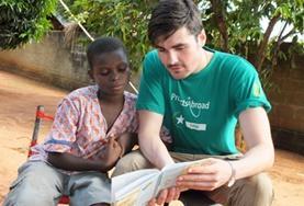 Een vrijwilliger in Togo helpt een scholier bij het lezen van een Engelstalig boek tijdens de groepsreis voor jongeren.
