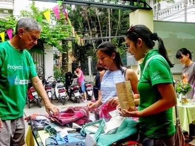 In Vietnam helpt een vrijwilliger bij de verkoop van goederen op een markt in Hanoi