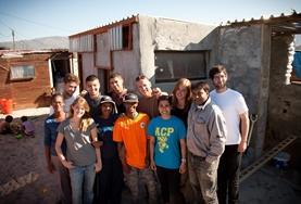 Een groep vrijwilligers van het community township project poseert voor een foto na een dag hard werken.