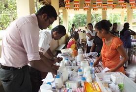 Een vrijwilliger van het farmacie project helpt bij de uitgifte van medicijnen tijdens een medical outreach in Sri Lanka.