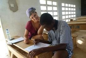 Een logopedie vrijwilliger helpt een man in Togo bij het doen van spraakoefeningen.