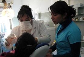 Een tandheelkunde vrijwilliger kijkt mee met ervaren Argentijnse tandartsen.