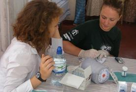 Een verloskunde vrijwilliger helpt in het ziekenhuis tijdens haar vrijwilligersproject in Sri Lanka.