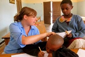 Een lesgeef vrijwilliger in Tanzania helpt de kinderen bij hun huiswerk.