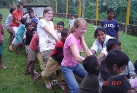 Vrijwilligers op het sociale project in Sri Lanka nemen deel aan de spelletjes op het schoolplein.