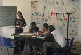 Een vrijwilliger geeft taallessen aan vluchtelingen in Italië.