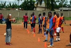 Een vrijwilliger geeft instructies aan het lokale voetbal team tijdens dit sport en voetbal project in Togo.